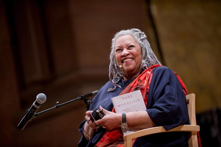 Photograph of Professor Toni Morrison holding a copy of her book